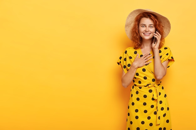Portrait of pleasant looking satisfied young redhead woman keeps palms on chest, feels impressed to hear heart piercing story over smartphone, wears stylish bright yellow summer outfit