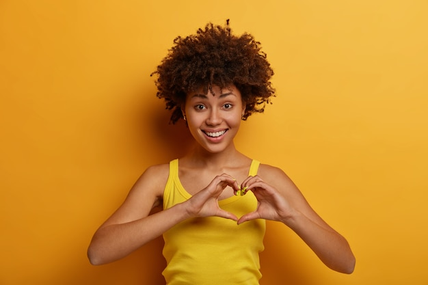 Portrait of pleasant looking woman makes heart gesture, says be my valentine, smiles positively, expresses love and care, fell in love with someone, wears yellow shirt, stands indoor alone.