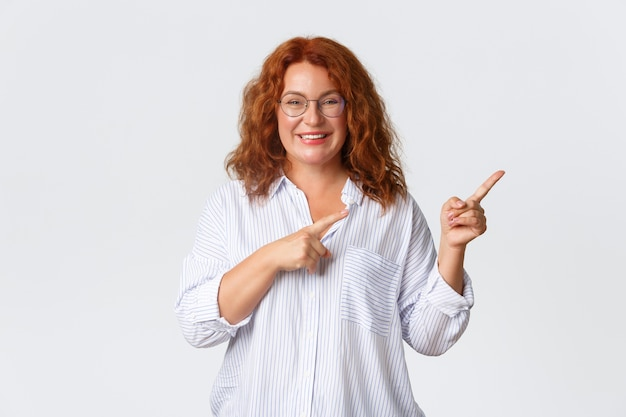Portrait of pleasant smiling middle-aged woman with red hair, wearing glasses and blouse showing advertisement, client of company recommend product or service, pointing right.