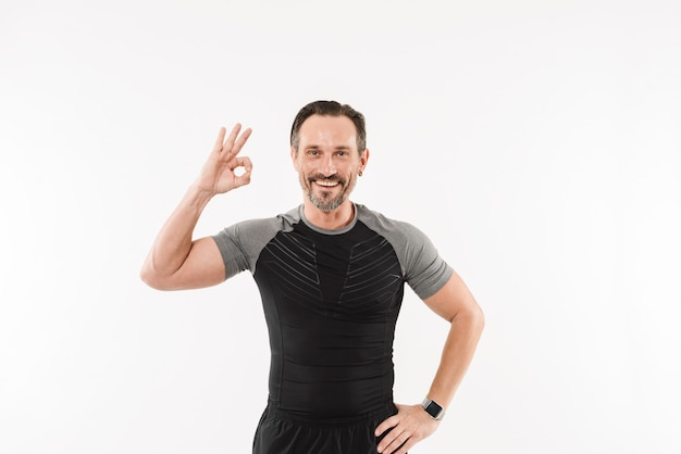 Portrait of pleased adult man fitness instructor smiling and gesturing ok sign after practising,