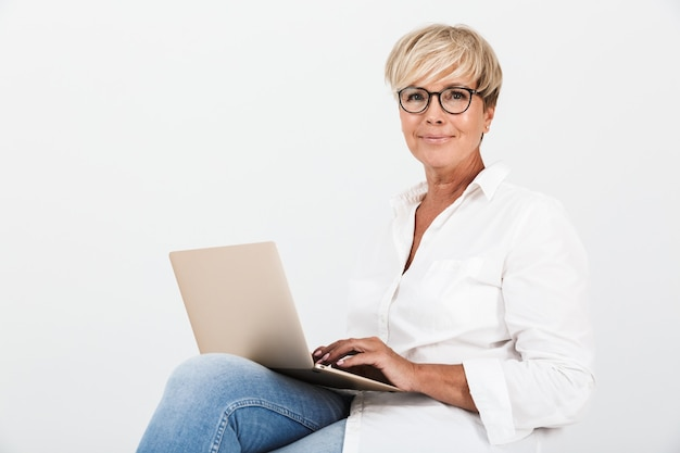 Portrait of pleased adult woman wearing eyeglasses smiling while sitting with laptop computer isolated over white wall in studio