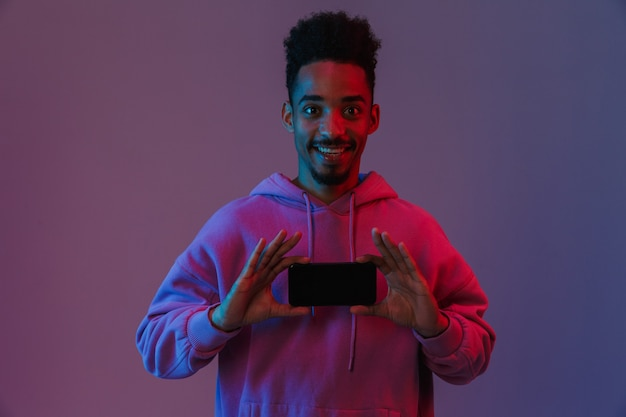 Portrait of pleased african american man in colorful hoodie smiling and holding cellphone isolated over violet wall