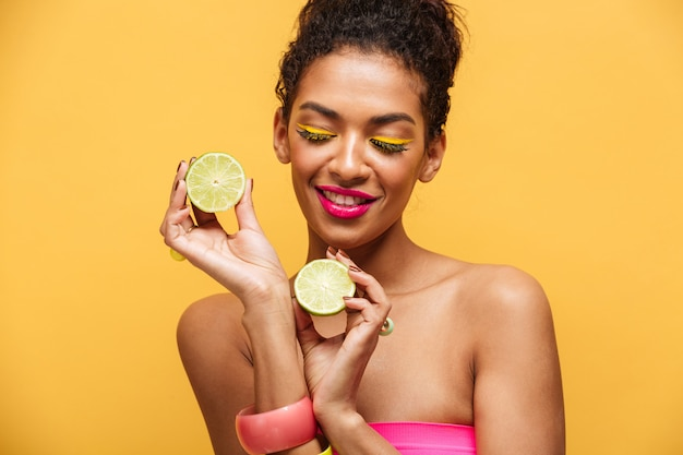 Portrait of pleased afro american woman with trendy makeup holding two halves of fresh lime in both hands isolated, over yellow wall