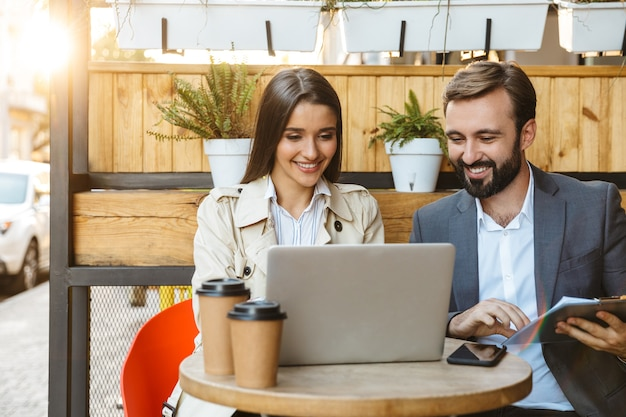 Portrait of pleased business couple man and woman in formal wear having conversation and working on laptop together while sitting in cafe outdoors