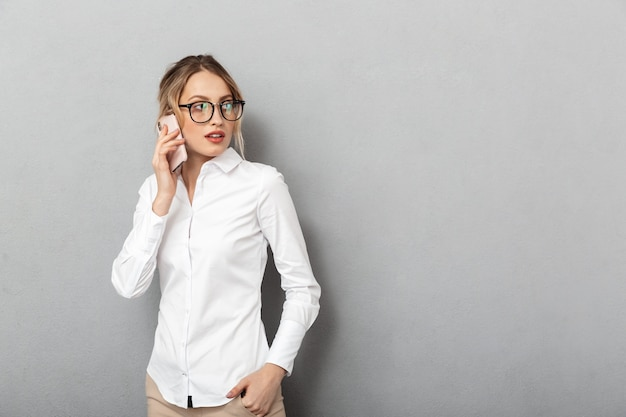 Portrait of pleased businesswoman wearing glasses smiling and speaking on mobile phone in the office, isolated