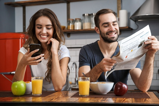 Portrait of pleased couple man and woman sitting at table in kitchen while having breakfast at home in the morning