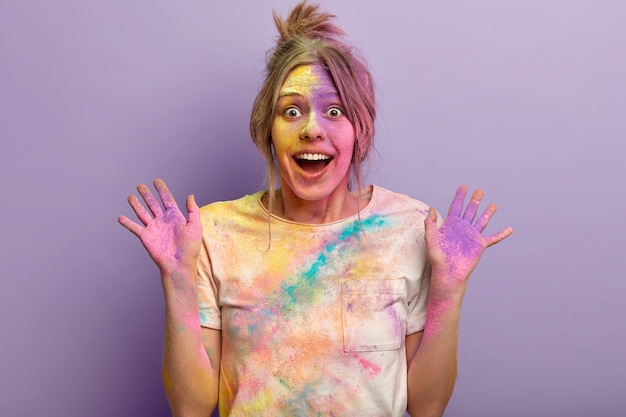 Portrait of pleased female has colored face, shows palms smeared with powder, expresses happiness and surprised reaction, poses against purple wall, celebrates traditional indian holiday