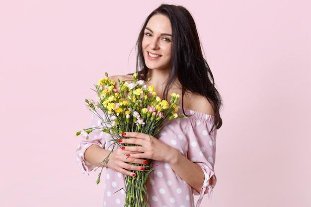 Portrait of pleased female model with dark hair, dressed in polka dot dress, smiles positively
