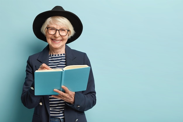 Portrait of pleased female pensioner writes plan strategy in diary, has nice clever look, wears glasses and black hat, isolated over blue wall with empty space. businesswoman with notepad