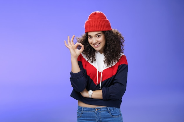 Portrait of pleased good-looking assertive woman with confident look and curly hair wearing warm winter hat showing okay gesture and smiling assuring, liking and approving awesome outfit of friend.
