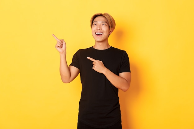 Portrait of pleased handsome asian guy in black t-shirt, pointing fingers and looking upper left corner with satisfied smile, yellow wall