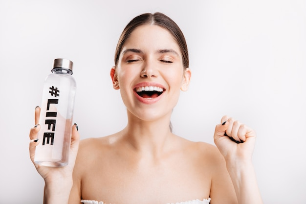 Portrait of pleased lady without makeup, posing with pleasure in great mood with bottle of water on isolated wall.