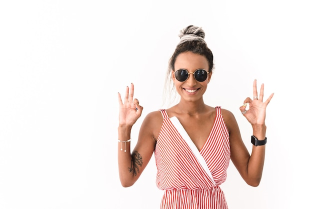 Portrait of a pleased optimistic happy young woman with dreads posing isolated on white showing okay gesture.