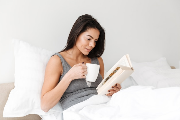 Portrait of pleased peaceful woman with long brown hair resting in comfortable bed after sleep, with reading book and drinking coffee