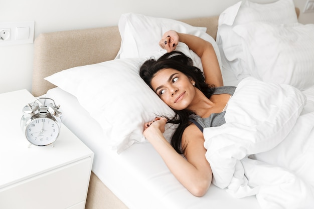 Portrait of pleased relaxed woman stretching in bed at bedroom with white clean linen, and looking on alarm clock on nightstand