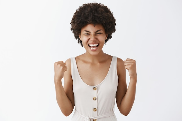 Portrait of pleased and satisfied happy good-looking dark-skinned female in white overalls raising fists in victory gesture yelling with triumph happily