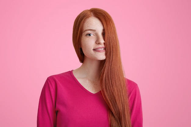 Portrait of pleased smiling young female with long ginger hair covering her face, models for well known magazine