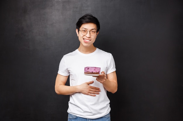 Portrait of pleased and staffed young cute asian man with piece of cake on plate