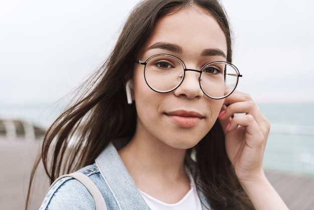 Portrait of pleased teenage girl wearing earpods and eyeglasses looking at front while walking along wooden pier by seaside