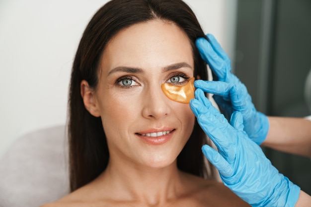 Portrait of pleased woman getting cosmetic procedure with patches by specialist in beauty salon