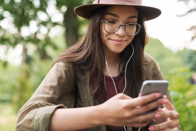 Portrait of pleased woman with long dark hair wearing hat and eyeglasses using earphones and smartphone in green park