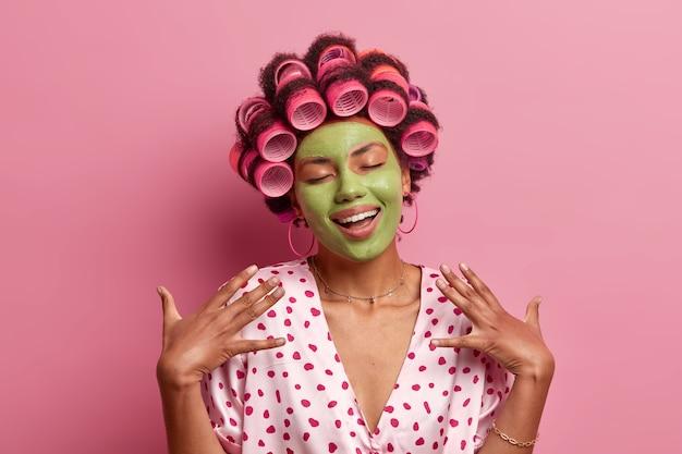 Ritratto di felice giovane donna afroamericana sta con gli occhi chiusi, sorride dolcemente, immagina qualcosa di carino, applica una maschera facciale verde, bigodini, sta al coperto