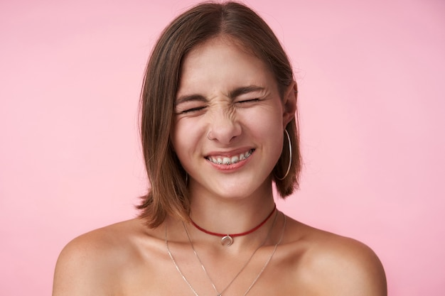 Portrait of plesant looking young short haired lady with natural makeup frowning her face while smiling cheerfully with closed eyes, isolated over pink wall