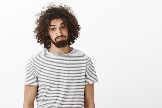 Ritratto di modello maschio attraente spensierato plyaful con barba e capelli ricci, che attacca fuori lingua e imbronciato, facendo facce buffe