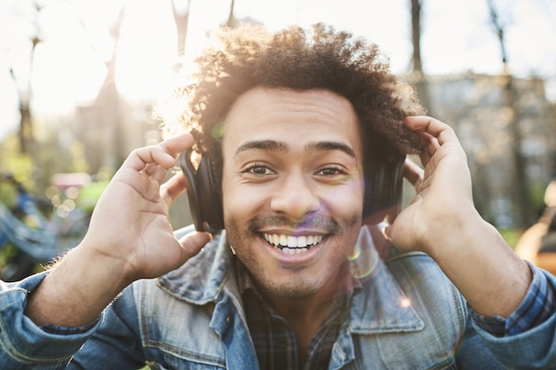 Portrait of positive adult dark-skinned man smiling broadly while sitting in park, listening to music in headphones and holding them with hands to hear better.