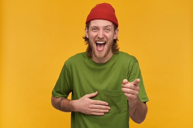 Ritratto di maschio adulto positivo con barba e acconciatura bionda. indossa una maglietta verde e un berretto rosso. ha un tatuaggio. ridere forte da te. isolato su muro giallo
