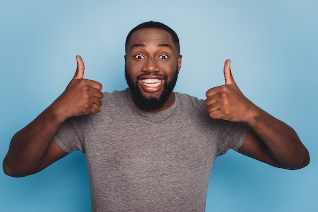 Portrait of positive afro american guy show thumb up sign isolated over blue background