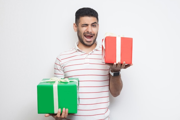 Portrait of positive attractive young adult man in t-shirt standing, holding two big gift box and winking, looking at camera. studio shot, white background, isolated, indoor, copy space