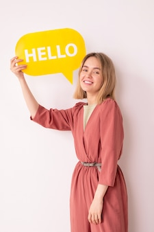 Portrait of positive attractive young woman in pink jumpsuit showing communication tag while saying hello