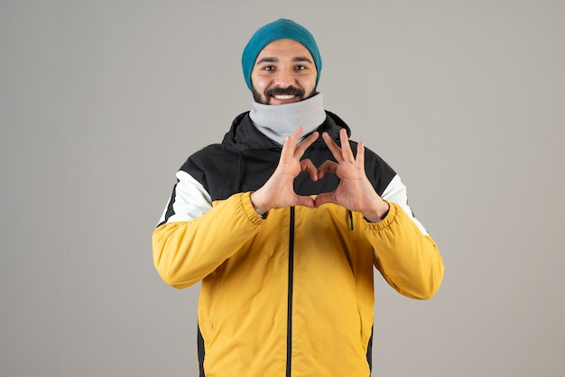 Portrait of positive bearded man in warm clothes standing and doing heart symbol with hands .
