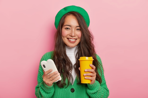 Portrait of positive brunette girl has coffee break after lectures, uses modern mobile phone for viewing pictures in social networks, sends notification to friend