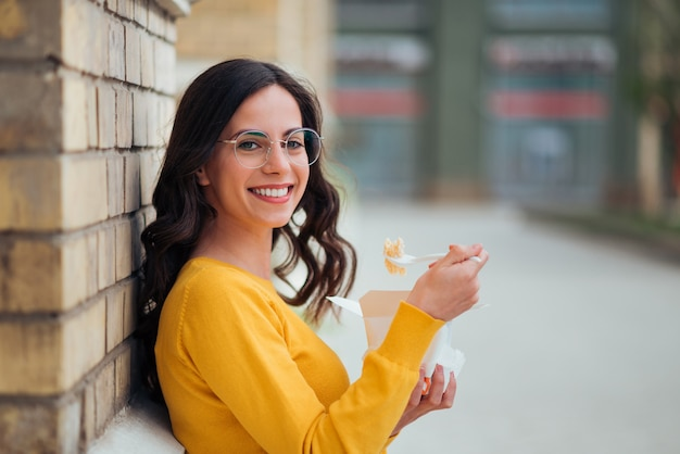 Portrait of a positive casual young woman eating take-away food on a break, looking at camera.