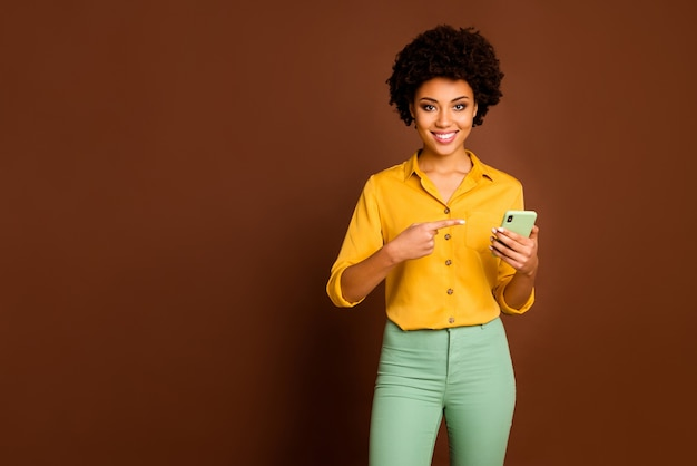 Portrait of positive cheerful afro american girl student use smartphone search online sales indicate point index finger device wear stylish yellow pants isolated brown color