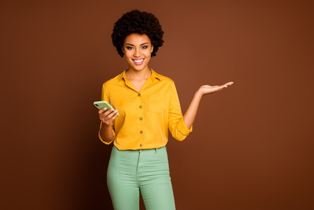 Portrait of positive cheerful afro american girl use smart phone hold hand present online adverts promotion social media sales wear yellow green outfit isolated over brown color