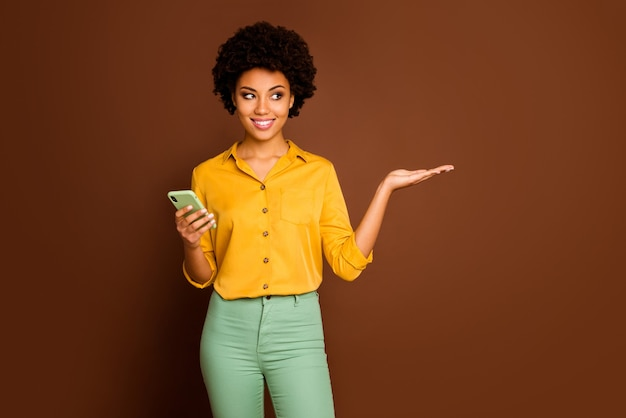 Portrait of positive cheerful afro american girl use smartphone hold hand display online social network discount recommend promotion ads wear yellow outfit isolated brown color