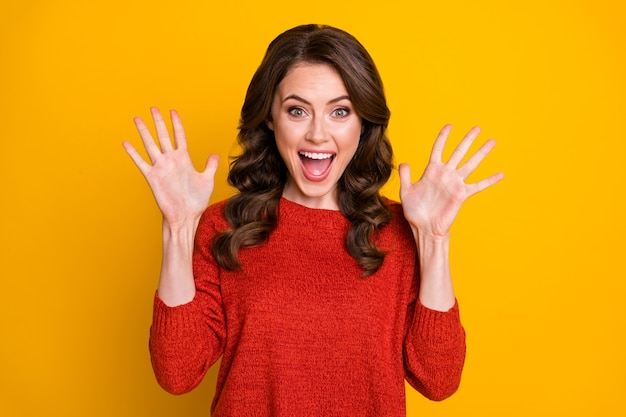 Portrait of positive cheerful astonished girl get long wait want gift present impressed raise hands wear sweater isolated over bright color background
