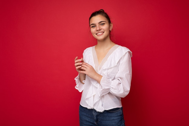 Portrait of positive cheerful fashionable woman in formalwear holding two hands together looking at camera isolated on red background with copy and empty space.