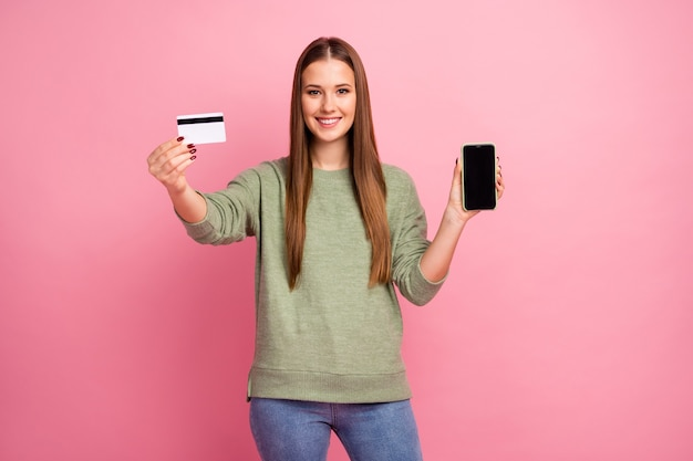 Portrait of positive cheerful girl hold cellphone debit card