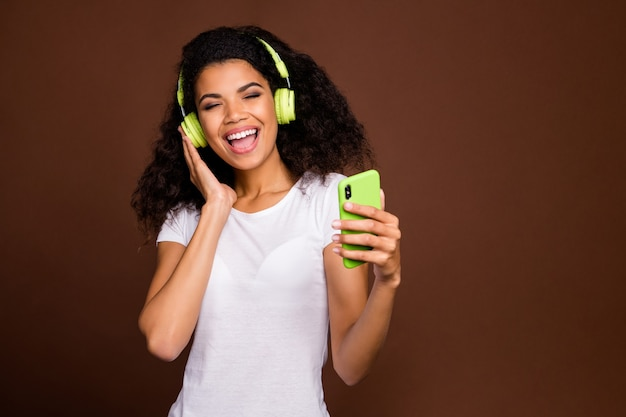 Portrait of positive cheerful girl listen music use cell phone playlist enjoy rest have green wireless ear phones wear modern white t-shirt.