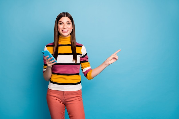 Portrait of positive cheerful girl point index finger use smartphone recommend online social media promotion wear stylish trendy clothing isolated over blue color wall