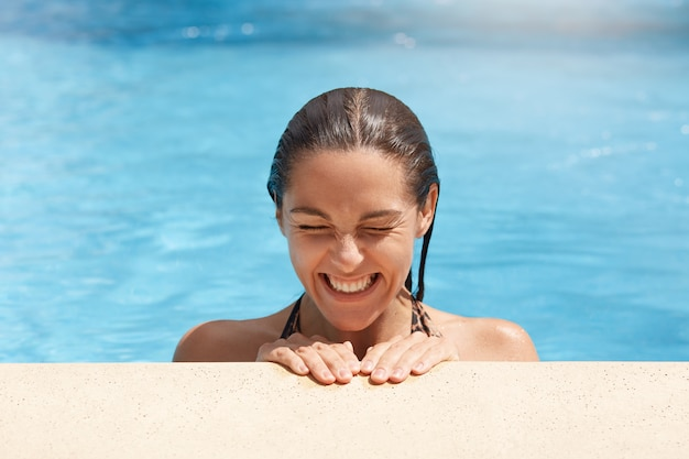 Portrait of positive cheerful good looking cute young brunette laughing sincerely, closing eyes, swimming alone, feeling good, being at spa resort, having wet hair. people and holidays concept.