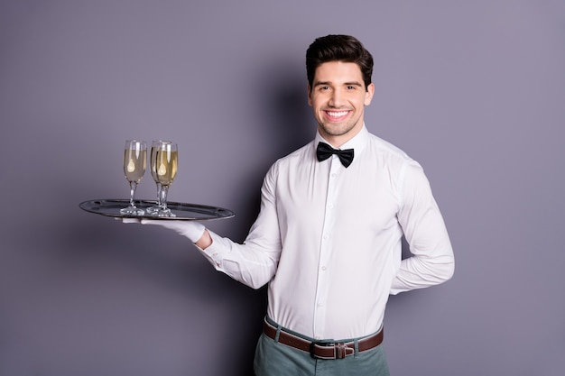 Portrait of positive cheerful restaurant staff worker waiter hold tray with alcohol give order to guest wear white shirt black bow isolated over grey color wall