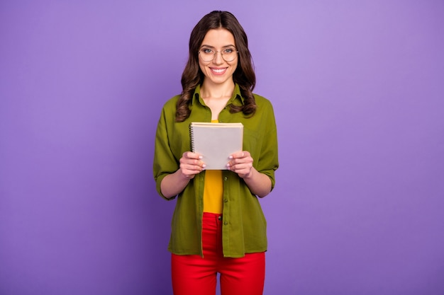 Portrait of positive cheerful smart girl hold note book prepare university lecture report wear trendy clothes isolated over purple color background