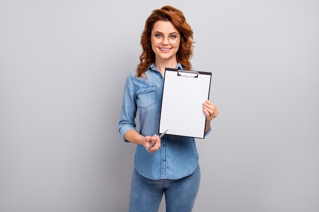 Portrait of positive cheerful smart manager woman hold paper clipboard point empty space pen for clients sign contract wear style trendy clothes isolated over grey color wall