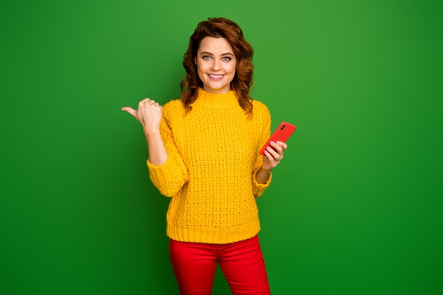 Portrait of positive cheerful social media promoter woman point forefinger copyspace use smartphone indicate ads promo wear jumper trousers isolated over bright shine color wall