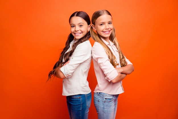 Portrait of positive cheerful team of two cute kids girls stand back-to-back ready solve school solutions decide decisions wear modern outfit isolated orange color background